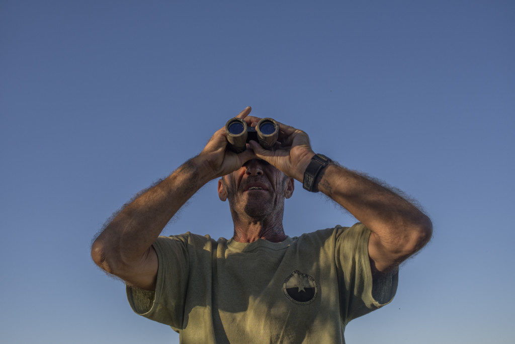 """OCTOBER 5 2014 BUENOS AIRES NATIONAL WILDLIFE REFUGE- Tim Foley, who goes by the handle, """"Nailer"""", eyes the hills with binoculars in the early morning."""