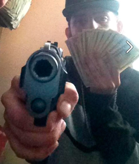 "A picture posted on the Facebook page for a user named ""Chriis Marley,"" shows the page's owner with a gun and money. Police say in an arrest warrant affidavit that ""Chriis Marley"" is an alias for Christopher Cruz. mpetroski@abqjournal.com Mon Aug 17 16:53:04 -0600 2015 1439851984 FILENAME: 197450.jpg"
